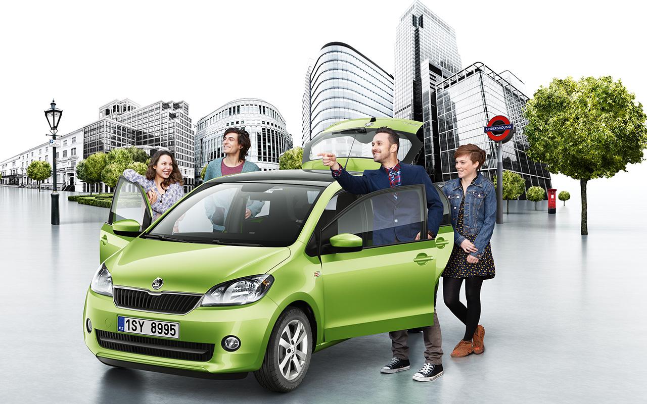 Vihreä Škoda Citigo parkkeerattu aukiolle, sen ovet ovat auki ja kaksi nuorta pariskuntaa seisoo auton vieressä katselemassa nähtvyyttä kuvan ulkopuolella.