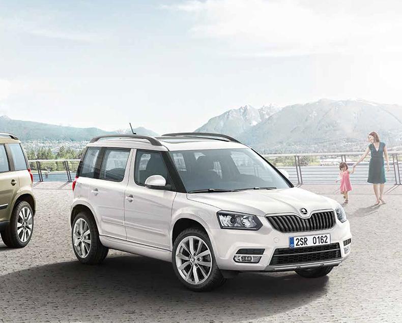 Hopeinen Škoda Yeti parkkeerattu järven rannalle. Järven takana siintää vuoria ja äiti lähestyy autoa tyttären kanssa.