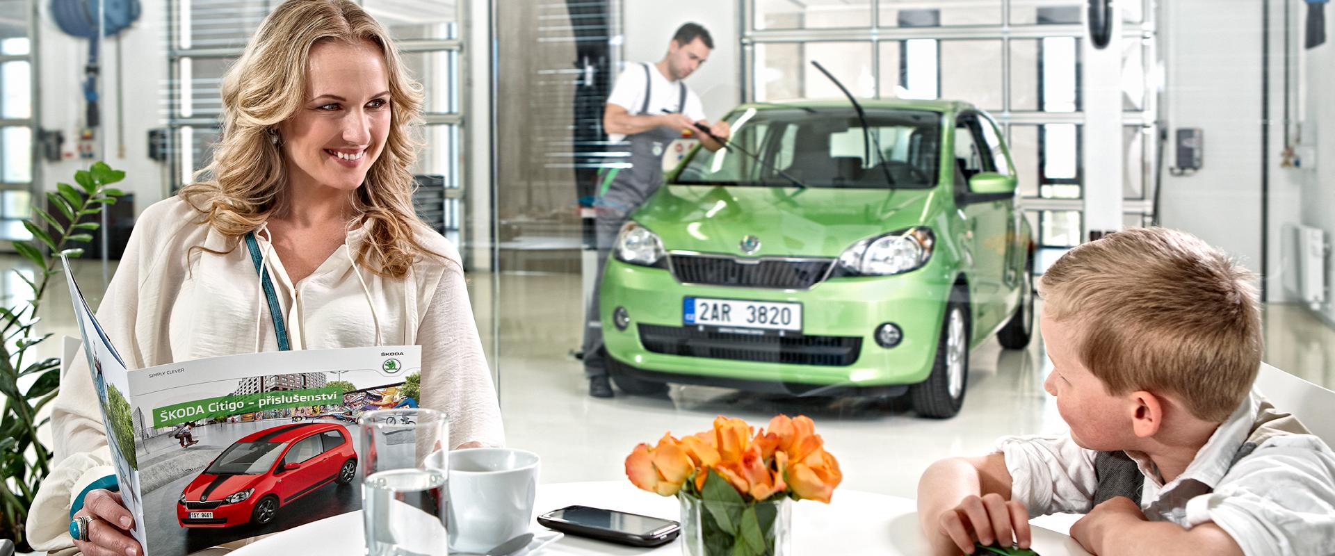 Nainen puhuu etualalla puhelimessa kahvia juoden, taustalla kaksi huoltoammattilaista huoltaa vihreää autoa.
