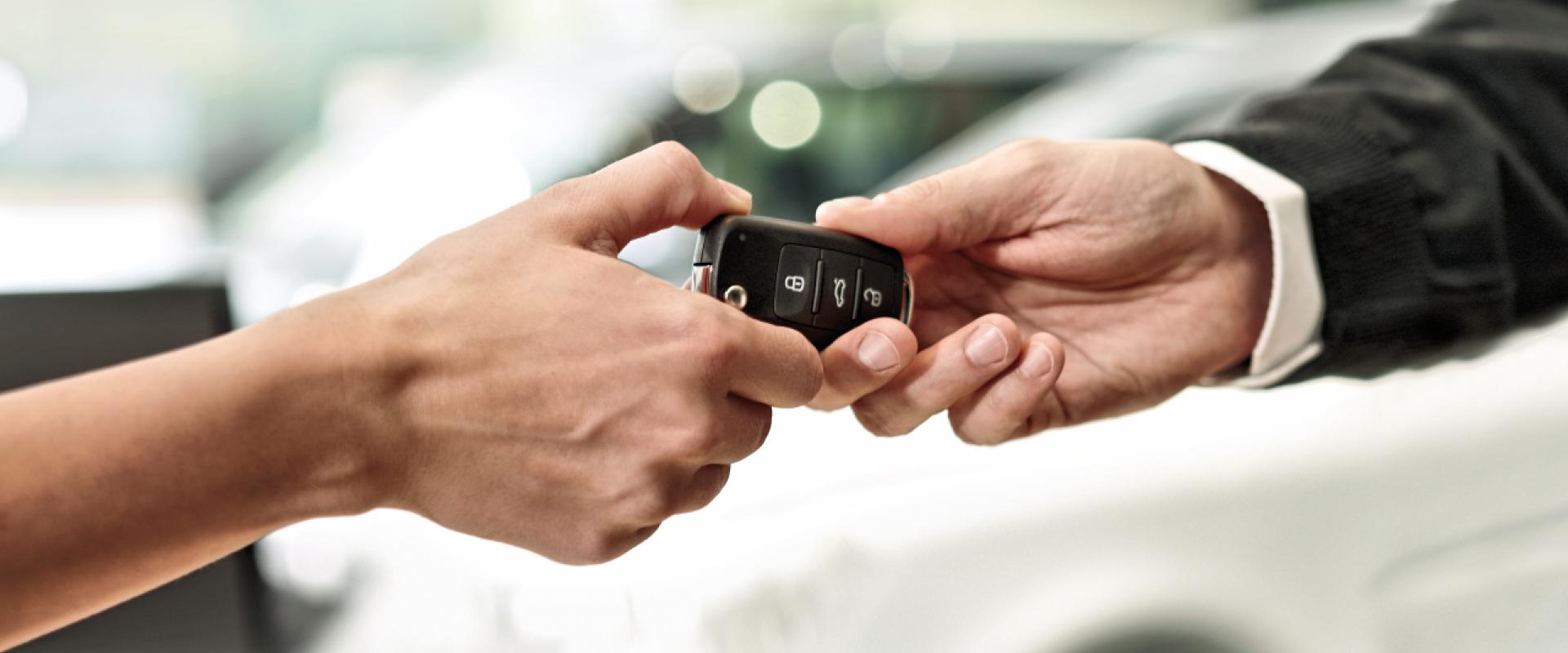 Perhe, äiti isä ja kaksi lasta, saavat auton avaimet automyyjältä.